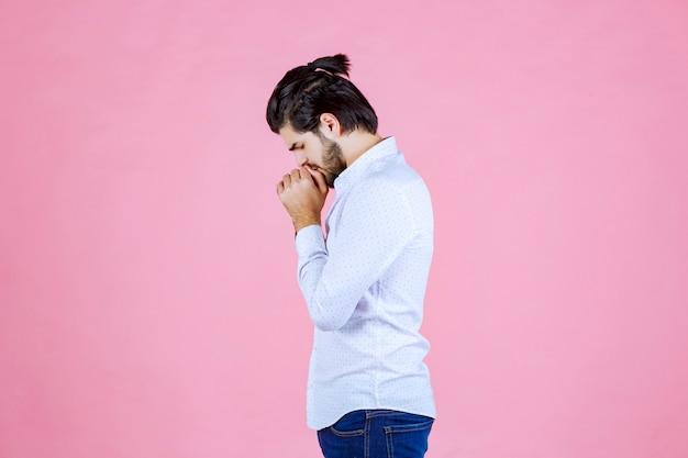 Mann in einem weißen hemd, das hände vereint und betet.