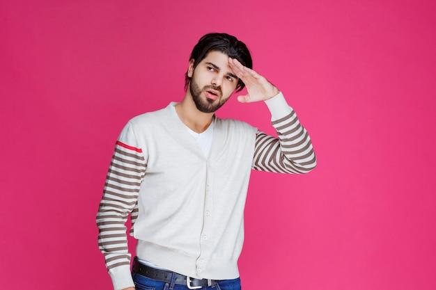 Mann in einem weißen hemd, das hand an seinen kopf legt und nach vorne schaut.