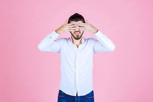 Mann in einem weißen hemd, das über seine finger schaut. Kostenlose Fotos