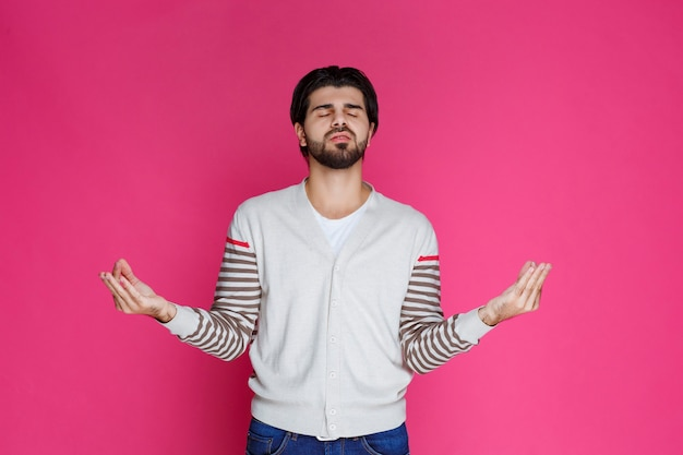 Mann in einem weißen hemd, das volle befriedigung oder meditationshandzeichen macht.