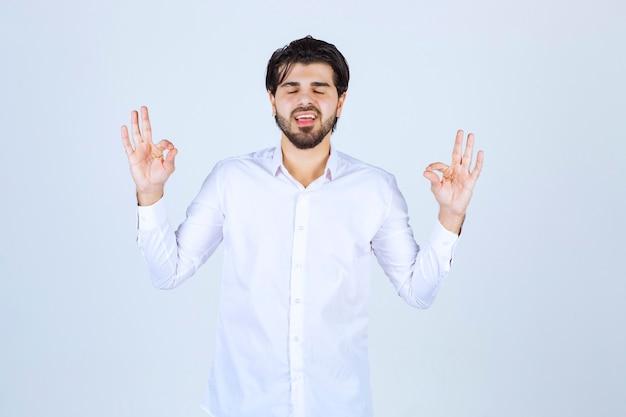 Mann in einem weißen hemd macht meditation