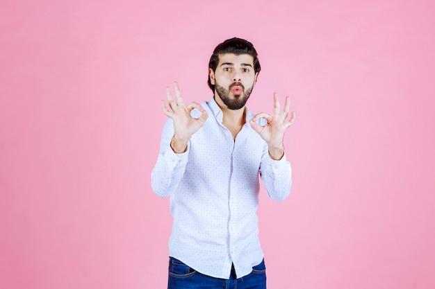 Mann in einem weißen hemd mit positivem handzeichen.