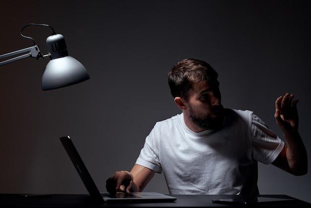 Mann in einem weißen t-shirt mit einem laptop und einem elektronischen tablet arbeitet am tisch