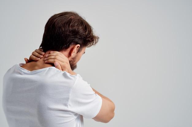 Mann in einem weißen t-shirt stress medizin schmerzen im nacken isoliert hintergrund
