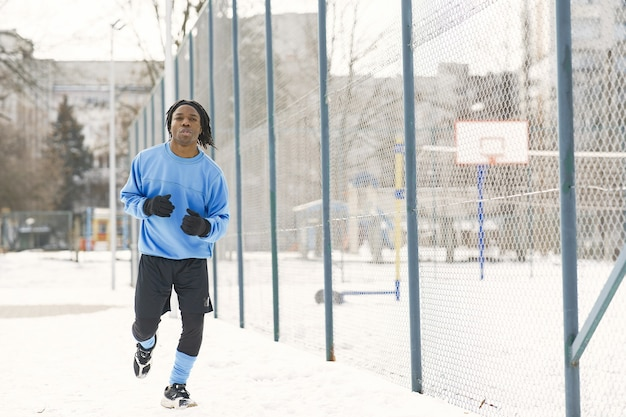 Mann in einem winterpark. afrikanischer typ, der draußen trainiert. mann rennen.