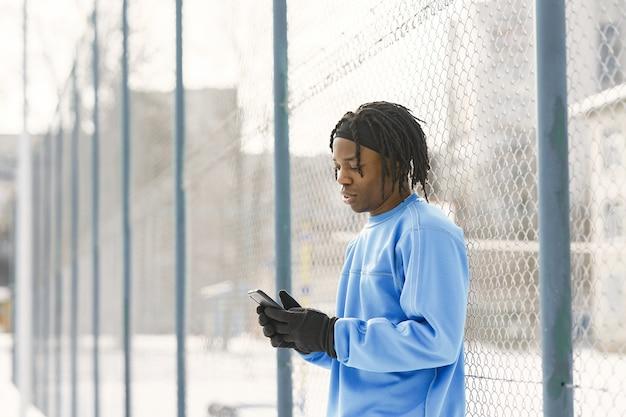 Mann in einem winterpark. afrikanischer typ, der draußen trainiert.