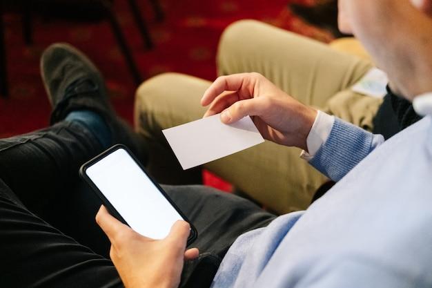 Mann in einer besprechung schaut auf eine visitenkarte und nutzt sein handy