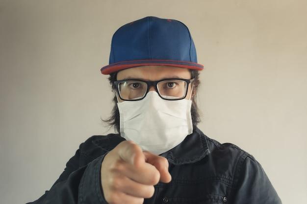Mann in einer blauen kappe zeigt auf sie und trägt eine weiße gesichtsmaske, um vor staub und coronavirus zu schützen