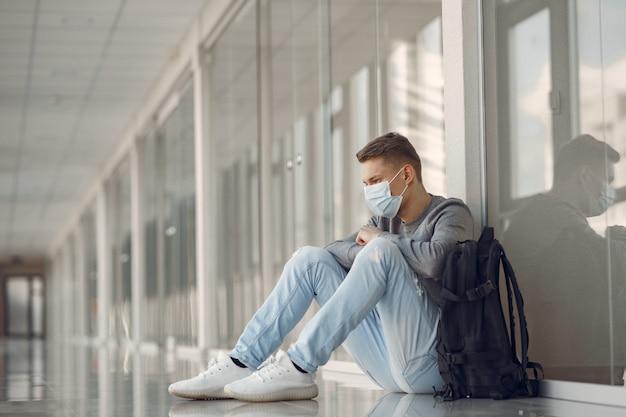 Mann in einer maske, die in der halle des krankenhauses sitzt