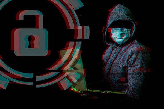 Mann in einer maske ohne gesicht und kapuze hält einen laptop in den händen auf einer dunkelheit