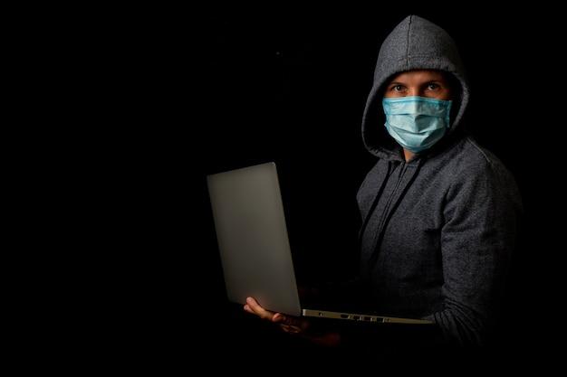 Mann in einer maske und einer kapuze hält einen laptop in seinen händen auf einer dunkelheit