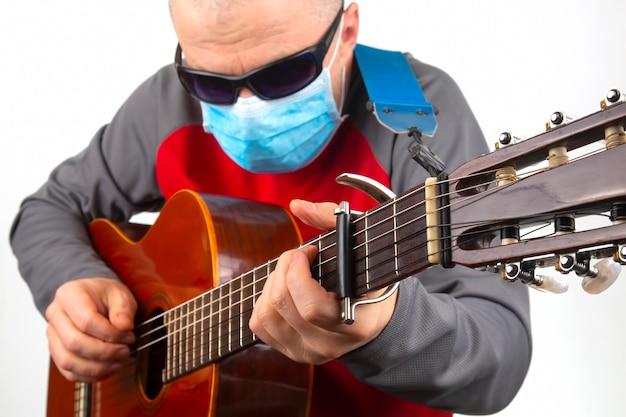 Mann in einer medizinischen maske spielt die klassische gitarre auf einem weißen hintergrund. musikalische kreativität. saitenmusikinstrument