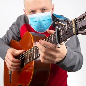 Mann in einer medizinischen maske spielt die klassische gitarre auf einem weißen raum. musikalische kreativität. saitenmusikinstrument
