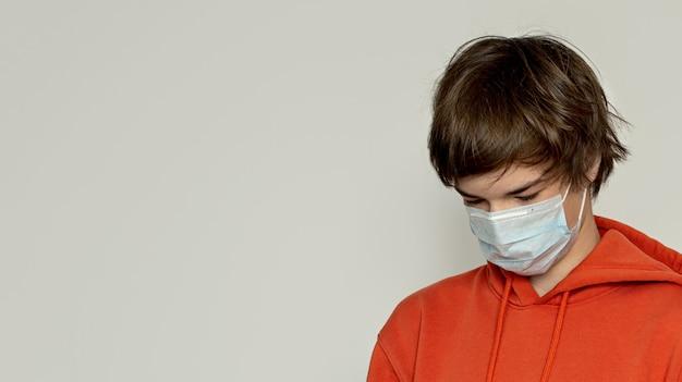 Mann in einer medizinischen maske und handschuhen hält eine box.