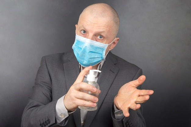 Mann in einer medizinischen schutzmaske während der quarantäne desinfiziert seine hände