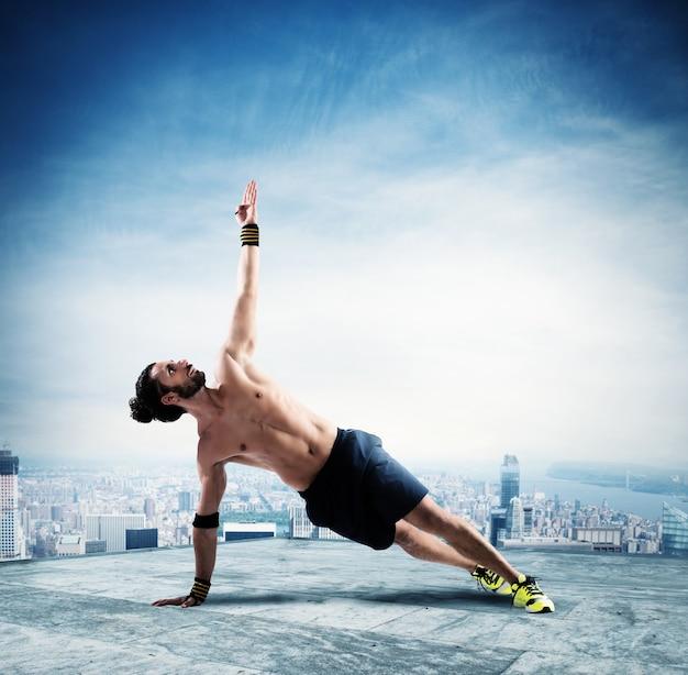 Mann in einer pilates-position über dem dach eines gebäudes