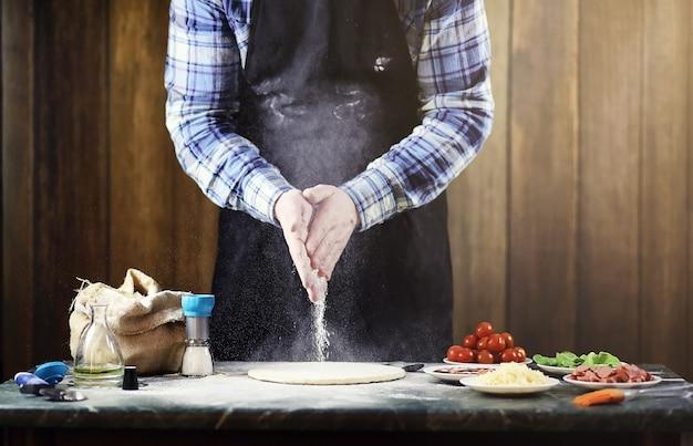 Mann in einer schürze bereitet eine pizza vor, knetet den teig und legt zutaten hinein