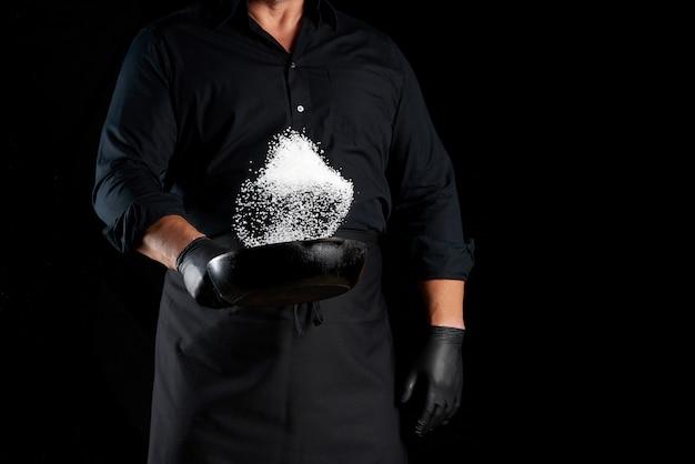 Mann in einer schwarzen uniform, die eine runde gusseisenpfanne mit salz hält, wirft der koch weißes salz auf einem schwarzen hintergrund
