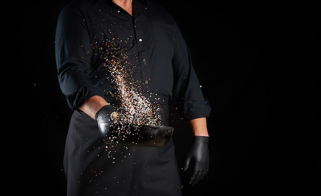 Mann in einer schwarzen uniform, die eine runde gusseisenpfanne mit salz und pfeffer hält, wirft kochgewürz auf einem schwarzen hintergrund, kopieren raum