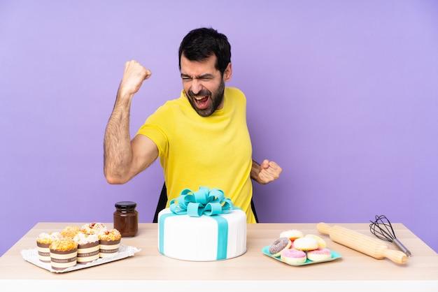 Mann in einer tabelle mit einem großen kuchen, der einen sieg feiert