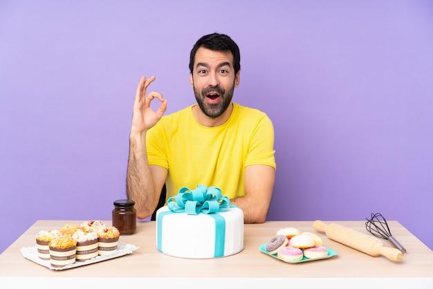 Mann in einer tabelle mit einem großen kuchen überrascht und okayzeichen zeigend