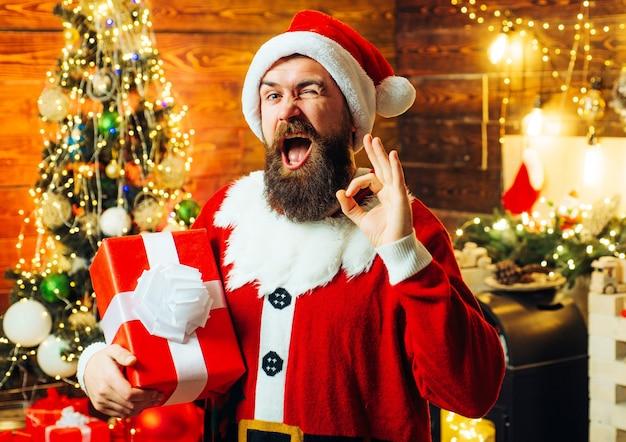 Mann in einer weihnachtsmannmütze mit einem geschenk
