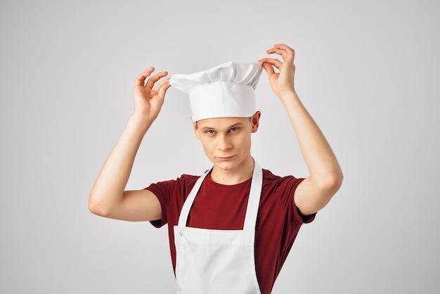 Mann in einer weißen schürze mit einer mütze auf dem kopf, der küchenuniform arbeitet