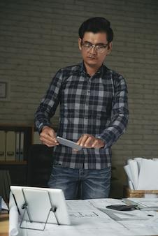 Mann in freizeitkleidung fertiges projekt auf seinem schreibtisch fotografierend