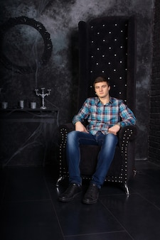 Mann in freizeitkleidung sitzt in einem stuhl mit hoher rückenlehne in einer unheimlichen halloween-haunted house-einstellung mit kandelabern und spinnweben