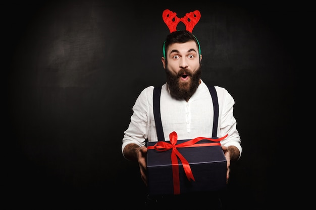 Mann in gefälschten hirschhörnern, die weihnachtsgeschenkbox über schwarz halten.