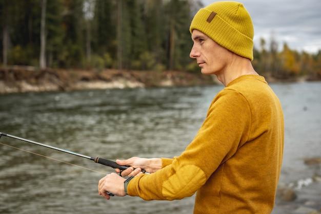 Mann in gelbem pullover und hut fischt am flussufer im herbstwald mit einer spinnrute in den händen