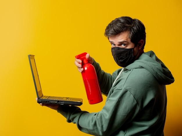 Mann in gesichtsmaske halten desinfektionsspray und notizbuch auf gelb