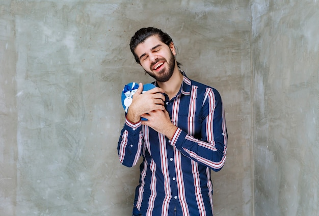 Mann in gestreiftem hemd, der eine blaue geschenkbox in herzform hält und sie umarmt, da sie sich sehr glücklich anfühlt