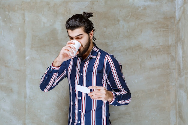 Mann in gestreiftem hemd, der eine tasse trinkt, während er eine visitenkarte hält