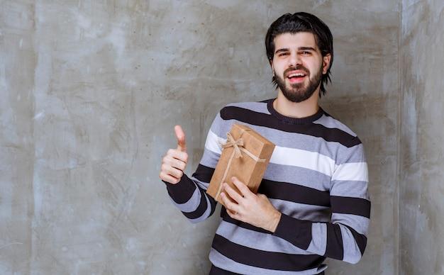 Mann in gestreiftem hemd hält eine geschenkbox aus karton und zeigt daumen hoch