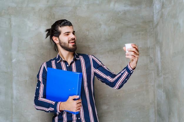 Mann in gestreiftem hemd mit blauem ordner und weißem einwegbecher