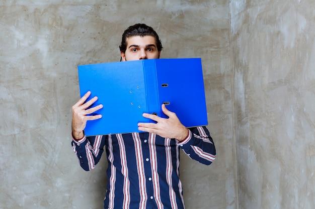 Mann in gestreiftem hemd mit blauem ordner