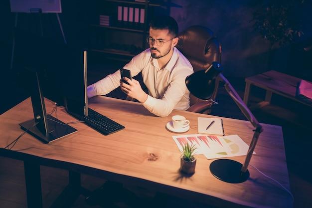 Mann in gläsern, der spät in der nacht arbeitet, hält telefon