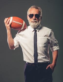 Mann in gläsern hält eine fußballkugel.