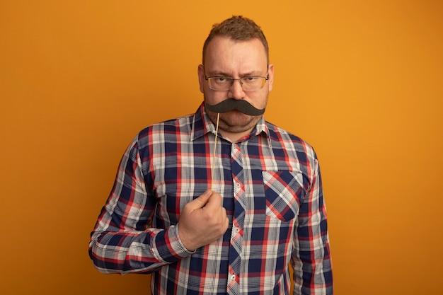 Mann in gläsern und kariertem hemd, das lustigen schnurrbart auf stock hält, der über orange wand steht