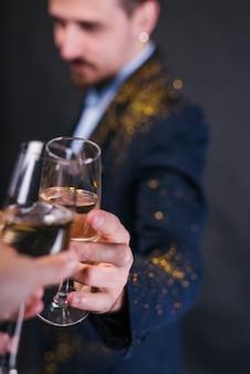 Mann in glitter pulver champagnerglas klopfen