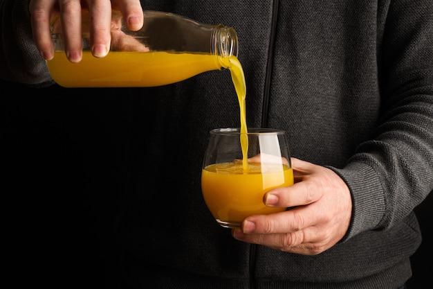 Mann in grau, der ein glas orangensaft serviert serving
