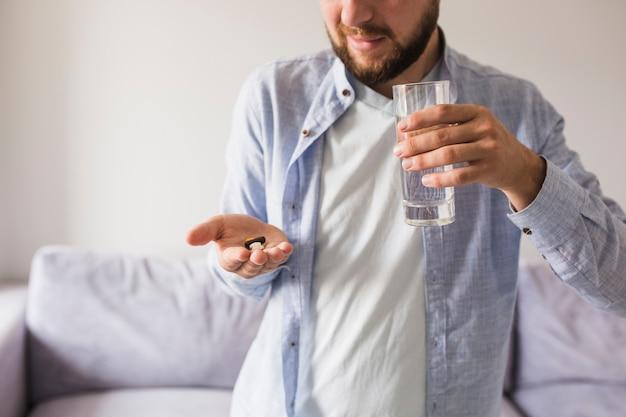 Mann in grau wird pillen und glas wasser