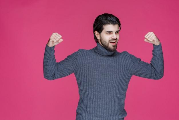 Mann in grauem pullover demonstriert seine fäuste und fühlt sich mächtig.