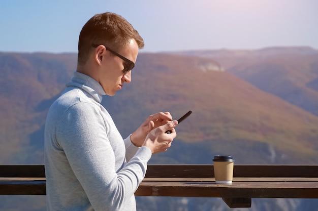 Mann in grauem rollkragenpullover und sonnenbrille mit telefon und plastikglas vor dem hintergrund der berge an einem klaren tag.