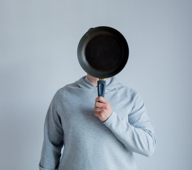 Mann in grauer kapuzenpulli holdng wanne auf gesichtsebene