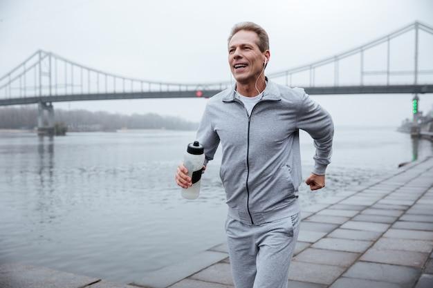 Mann in grauer sportbekleidung, der mit einer flasche wasser in der nähe des flusses läuft