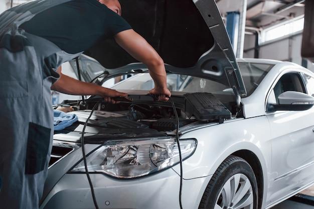 Mann in grauer uniform repariert weißes auto drinnen