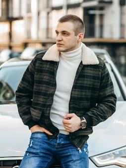 Mann in grüner karierter jacke mit weißem luxusauto