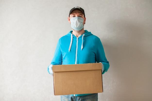 Mann in gummihandschuhen und einer medizinischen maske liefert karton